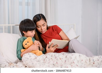 Asian mother work home together with son. Mom and kid reading fairy tale before sleep on the bed. Woman lifestyle and family activity.
