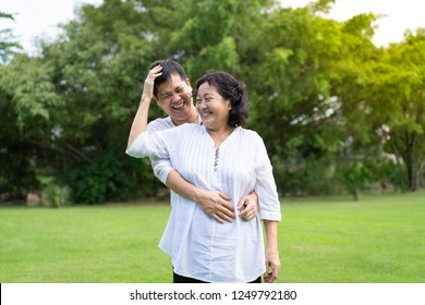 Asian mother and young son are standing and hugging together in the park with fully happiness moment, concept of adult son take care elderly mother in family lifestyle