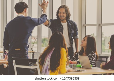 Asian and Multiethnic Business people with casual suit standing and Hand coordination with happy action for teamwork in the modern workplace, people business group concept