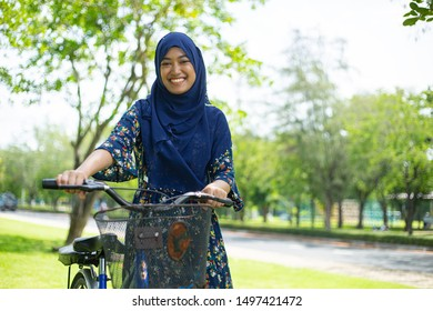 Asian musalim holding bicycle and smiling in the garden.