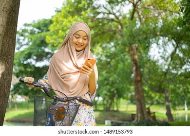 Asian musalim woman looking smartphone for search and chat with her friend.