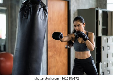 Asian muscular focused woman has boxing training by punching sand bag in fitness gym to practice Muay Thai. Sport, bodybuilding, and healthy lifestyle concept.