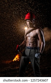 Asian muscular man black hair and bread serious face topless cross rescue rope on torso and holding fire axes in right hand standing in dark fire smoke and pouring rain background