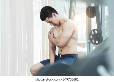 Asian Muscular man having pain on his shoulder while working out at the gym. copy space.