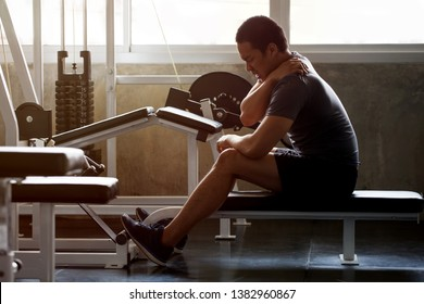 asian Muscular man suffering from shoulder injury while exercising at gym in morning light . workout , exercises , bodybuilder training , sport guy rubbing his back and neck pain .  backache