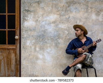 Asian musician man in casual dress sitting on chair and playing ukulele with classic cement wall and wooden door background