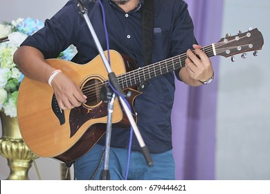 Asian musician playing acoustic guitar on stage background.