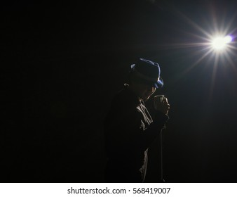 Asian Musician  singing a song with microphone on black background with spot light and lens flare,musical concept