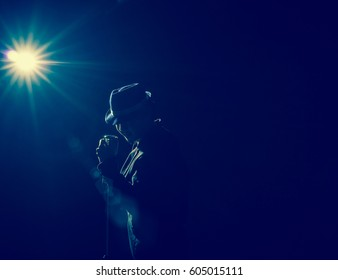 Asian Musician  singing a song with microphone on black background with spot light and lens flare, musical concept