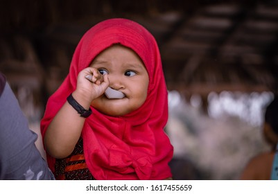 Asian Muslim baby girl wearing a red hijab is eating alone using a plastic spoon. Cute baby expression.