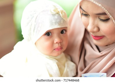 Asian Muslim baby little girl crying while with her mother in the garden