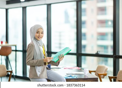 Asian Muslim businesswoman in hijab head scarf working with paper document in the modern office. businesspeople, diversity and office concept