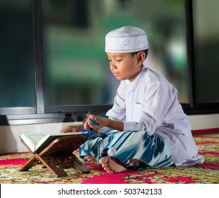 Asian muslim child with smile face reads the holy Quran(the public item of all muslims ).