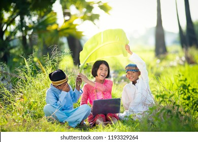 Asian Muslim children brother and sister playing laptop at outdoor Countryside,Knowledge,education and technology concept.