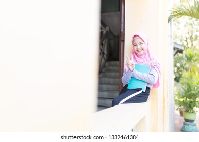 asian muslim children holding book with her hand, islamic student sitting in school, she feeling happy and smile