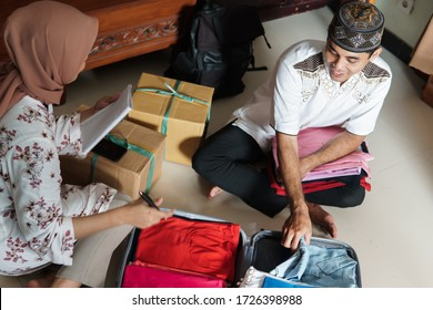 Asian Muslim couple prepare packing clothes for eid mubarak holiday