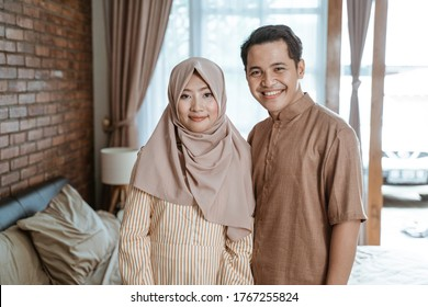 Asian Muslim couples smile happily when looking at the camera standing in the room