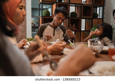 asian muslim family break fasting together in dining room. buka puasa in ramadan