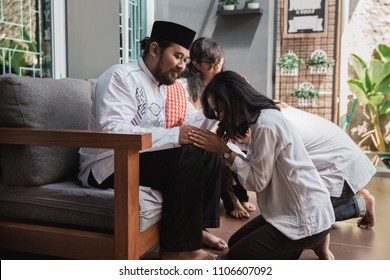 asian muslim family during eid mubarak celebration. forgiving and apologizing each other