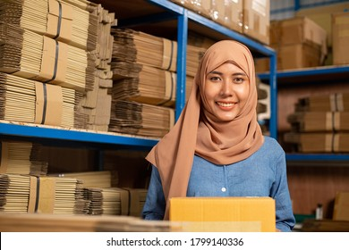Asian muslim  holding box for prepare to deliver to customer.Thai woman packing product in the warehouse.Smiling face working in storehouse for sending goods.