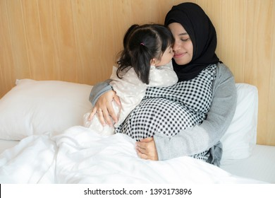 Asian Muslim Indonesian pregnant woman and her daughter holding hands on her belly on the bed. 36 weeks of pregnant. family concept.