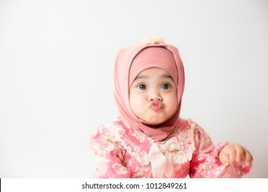 Asian Muslim little girl making a cute pucker face isolated on white background.  face expression
