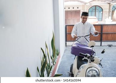 asian muslim male travelling for eid mubarak lebaran by motorcyle. mudik balik kampung concept by motorbike