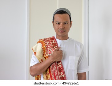 asian muslim man bring prayer mat (sajadah)