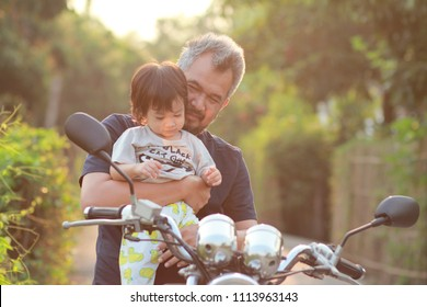 Asian Muslim man with his little boy on motorcycle.Father and son smile with happy face,light shining from the back with morning background.Concept of Father and son,Modern Masculinity and Femininity