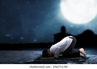 Asian Muslim man in praying position (salat) on prayer rug with the night scene background - Shutterstock ID 1962711769