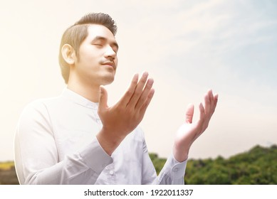 Asian Muslim man standing while raised hands and praying with sunlight background