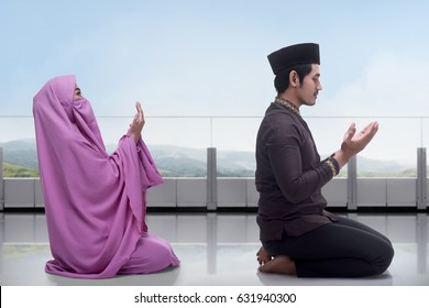 Asian muslim man and woman praying together with view landscape background