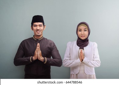 Asian muslim man and woman with traditional dress praying together over grey background