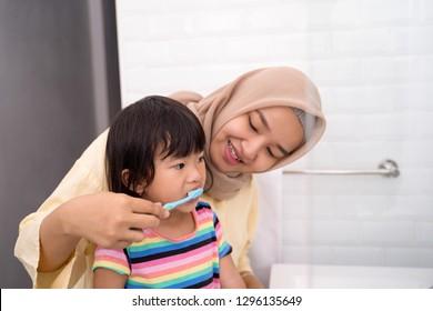 asian muslim mom brush her kid's teeth in the bathroom