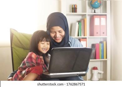 Asiatische Mama und kleine Tochter von Müttern und Mädchen, die online lernen oder Videos auf Laptop anschauen, Glück zwischen Mutter und Kind, Alleinerziehende und glückliches Konzept