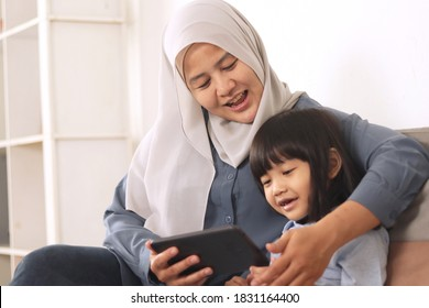 Asian muslim mom and little baby girl daughter learning online or watching videos on tablet phone, happiness between mother and kid, single parent being happy concept