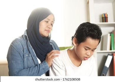 Asian muslim mother calming comforting her sad boy son, supportive mom help her teenage kid