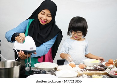 Asian Muslim mother and cute daughter preparing the dough to make a cake in kitchen room at home. Messy kitchen. Motherhood concept. Happy Family
