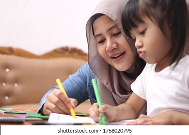 Asian muslim mother drawing with her daughter, single mom teaching baby girl, happy family concept