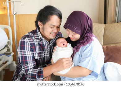Asian Muslim mother and father holding,hugging newborn or baby with love. nursing,care and love concept.