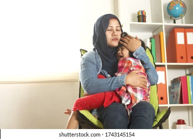 Asian muslim mother wearing hijab calming her sad and crying daughter, single mom and baby girl together