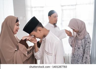 asian muslim parent shake hand in idul fitri eid mubarak celebration. family islam tradition