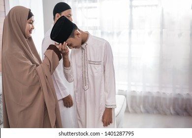 asian muslim parent shake hand in idul fitri eid mubarak celebration. family islam tradition