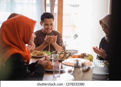 asian muslim people praying before having their food in dining room together for break fasting