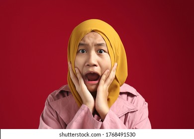 Asian muslim teenage young girl wearing hijab hold her cheek and terrified looking at camera, shocked worried gesture with open mouth, cant believe of bad thing that she see, against red background
