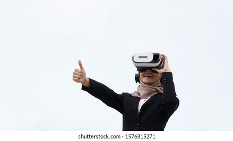 Asian muslim teenager with hijab using a VR googles showing thumbs up isolated on white background.