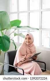 asian muslim woman browsing with tablet while relaxing sitting on a couch
