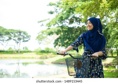 Asian muslim woman with her bicycle in the outdoor.