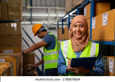 Asian muslim woman holding blue color file clamp for record goods product. Two warehouse worker work in warehouse by note and scan barcode.
