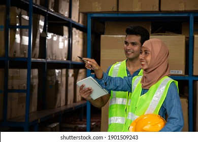 Asian muslim woman pointing stock product for record goods product. Two warehouse worker work in warehouse by note and scan barcode.